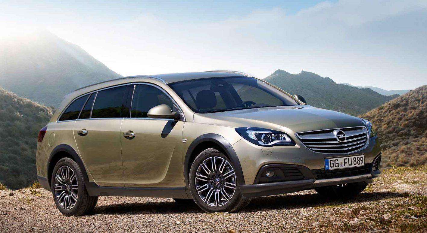 Opel Insignia Country Tourer, metallik sølvgrønn kjører i fjellandskap på grusvei i fint vær.